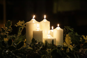 Image of lit candles in the centre of a large evergreen festive wreath